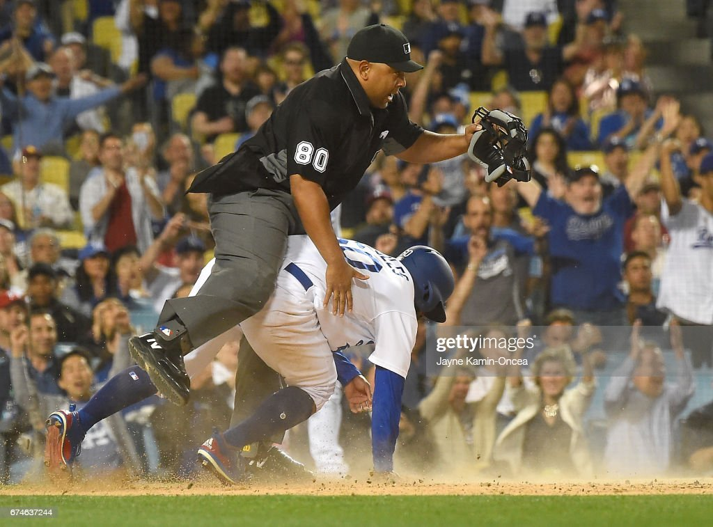 Andrew Toles #60 of the Los Angeles Dodgers collides with umpire Adrian Johnson #88 as he scores on a passed ball by Jerad Eickhoff #48 of the Philadelphia Phillies in the third inning of the game at Dodger Stadium on April 28, 2017 in Los Angeles, California.