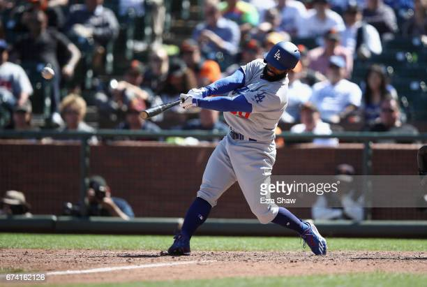 Andrew Toles of the Los Angeles Dodgers hits a single that scored Ross Stripling in the 10th inning against the San Francisco Giants at ATT Park on...