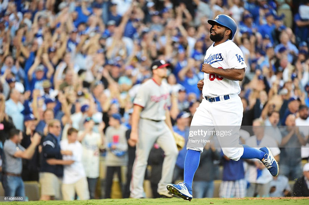 Andrew Toles #60 of the Los Angeles Dodgers scores on a single by Chase Utley #26 as Oliver Perez #46 of the Washington Nationals looks on in the eighth inning during game four of the National League Division Series at Dodger Stadium on October 11, 2016 in Los Angeles, California.