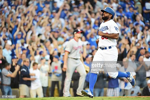Andrew Toles of the Los Angeles Dodgers scores on a single by Chase Utley as Oliver Perez of the Washington Nationals looks on in the eighth inning...