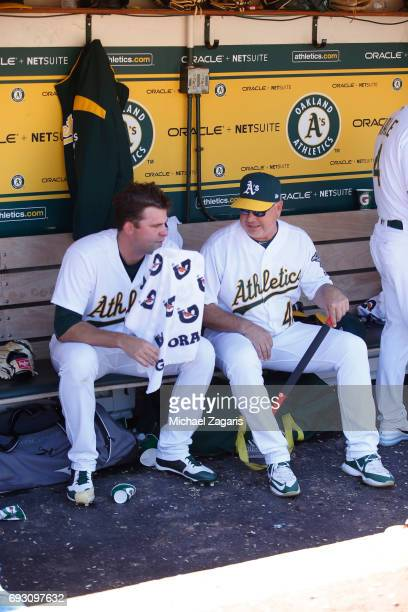 Andrew Triggs and Pitching Coach Curt Young of the Oakland Athletics talk in the dugout during the game against the Boston Red Sox at the Oakland...