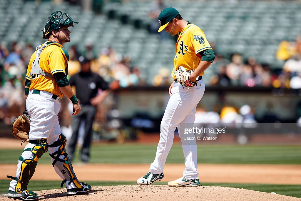 Andrew Triggs #60 of the Oakland Athletics reacts in front of Stephen Vogt #21 after giving up a two run double to Pedro Alvarez (not pictured) of the Baltimore Orioles during the fourth inning at the Oakland Coliseum on August 11, 2016 in Oakland, California. The Baltimore Orioles defeated the Oakland Athletics 9-6.