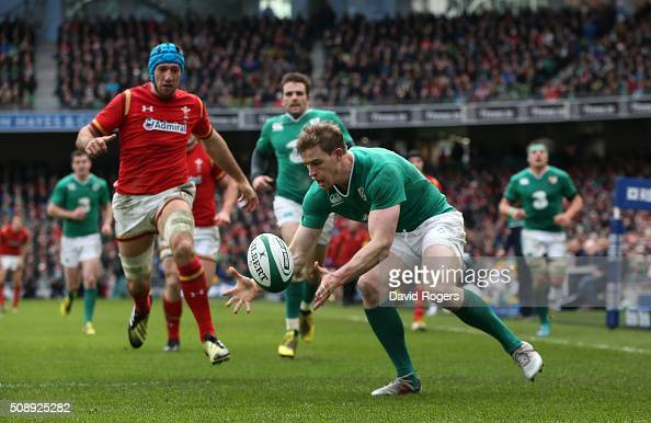 Andrew Trimble of Ireland gathers the ball behind his own tryline as Justin Tipuric of Wales closes in during the RBS Six Nations match between...