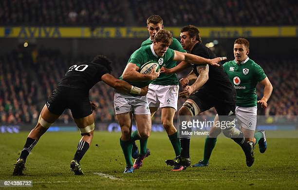 Andrew Trimble of Ireland is tackled by Ardie Savea of New Zealand and Liam Squire of New Zealand during the International match between Ireland and...