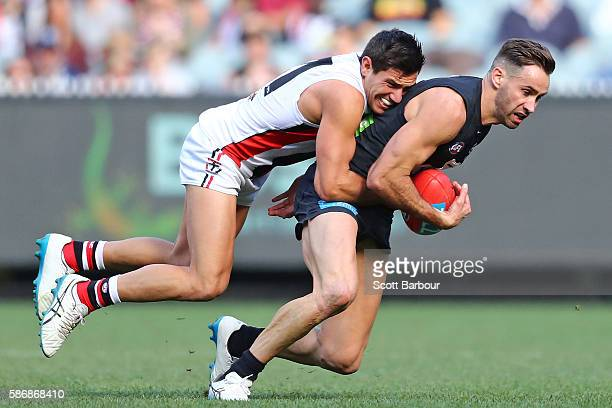 Andrew Walker of the Blues is tackled by Darren Minchington of the Saints during the round 20 AFL match between the Carlton Blues and the St Kilda...