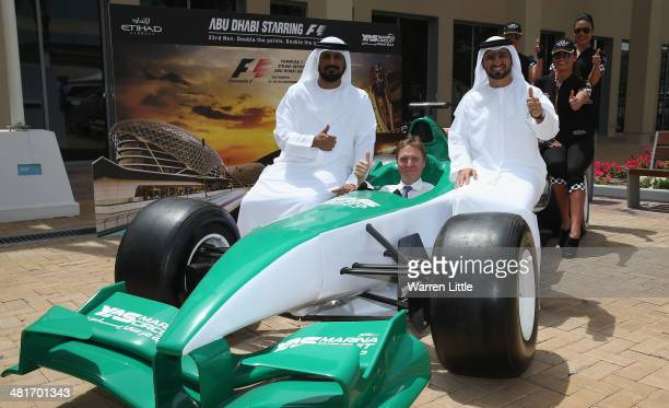 Andrew Ward Vice President Marketing Etihad Airways sits in a race car flanked by Al Tareq Al Ameri Chief Executive Officer Yas Maria Circuit and...