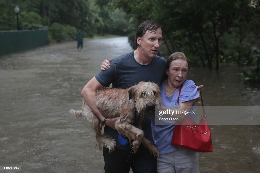 Andrew White (L) helps a neighbor down a street after rescuing her from her home in his boat in the upscale River Oaks neighborhood after it was inundated with flooding from Hurricane Harvey on August 27, 2017 in Houston, Texas. Harvey, which made landfall north of Corpus Christi late Friday evening, is expected to dump upwards to 40 inches of rain in Texas over the next couple of days.