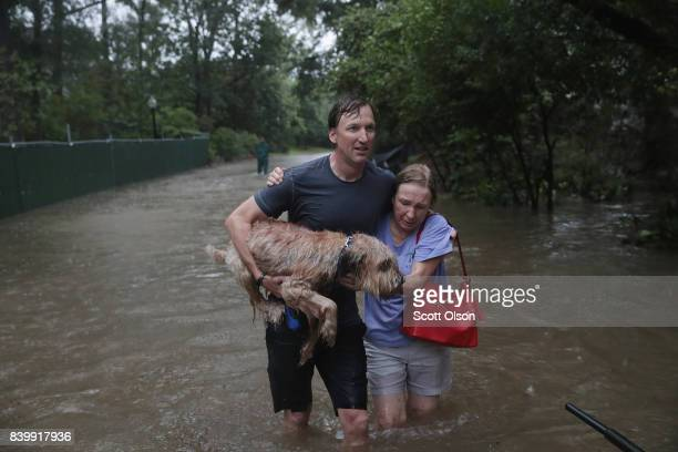 Andrew White helps a neighbor down a street after rescuing her from her home in his boat in the upscale River Oaks neighborhood after it was...