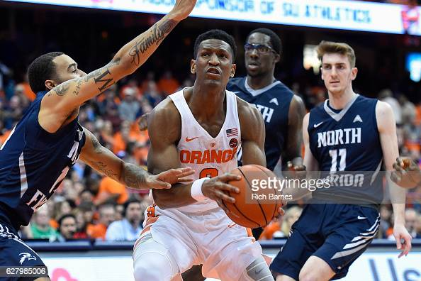 Andrew White III of the Syracuse Orange drives to the basket between a group of North Florida Ospreys defenders during the second half at the Carrier...
