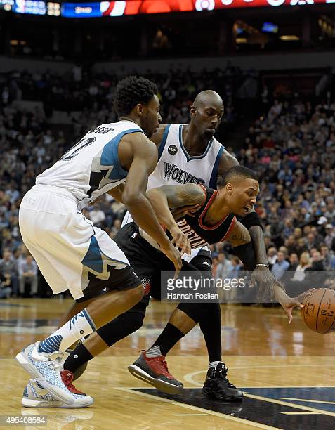 Andrew Wiggins and Kevin Garnett of the Minnesota Timberwolves defend against Damian Lillard of the Portland Trail Blazers during the first quarter...