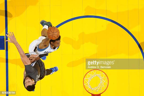 Andrew Wiggins of the Minnesota Timberwolves dunks the ball JaVale McGee of the Golden State Warriors during the game on November 26 2016 at ORACLE...
