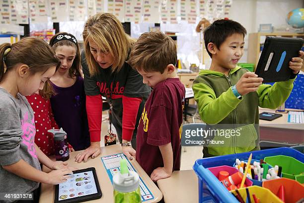 Andrew Zhu right smiles while using his iPad for a lesson as first grade teacher Jan Sabin helps Hayden Putz left with her work on Friday Jan 16 at...