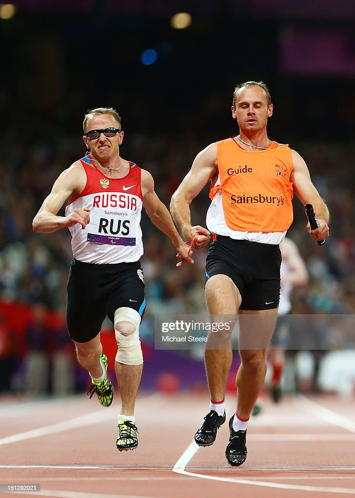 Andrey Koptev of Russia and his guide cross the line to win gold in the Men's 4x100m relay T11/13 Final on day 7 of the London 2012 Paralympic Games at Olympic Stadium on September 5, 2012 in London, England.