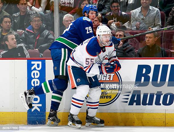 Andrey Pedan of the Vancouver Canucks checks Mark Letestu of the Edmonton Oilers during their NHL game at Rogers Arena December 26 2015 in Vancouver...