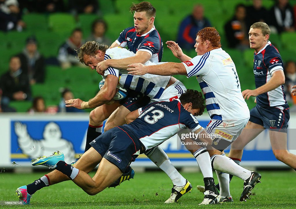 Andries Bekker of the Stormers is tackled by Mitch Inman and Jason Woodward of the Rebels during the round 14 Super Rugby match between the Rebels...