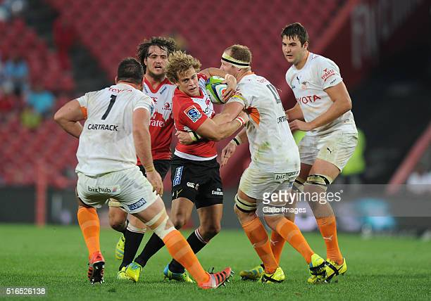 Andries Coetzee of Lions is tackled by Charles MariasCarl Wgner and Lood de Jager of Cheetahs during the Super Rugby match between Emirates Lions and...