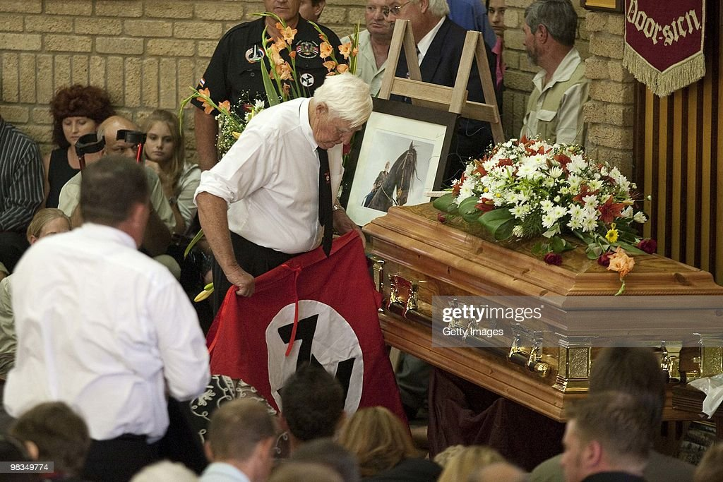 Andries TerreBlanche rolls up the AWB movement's flag during the funeral of Afrikaner Resistance Movement (AWB) slain leader Eugene Terre'Blanche on April 9, 2010 in Ventersdorp, South Africa. Some 3,000 people attended the funeral of the white supremacist who was murdered last Saturday at his farm. Two of Terrblanche's employees have been charged with his murder. Andries TerreBlanche is the brother of the late AWB leader.