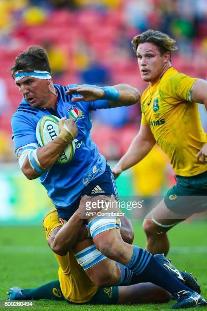 Andries Van Schalkwyk of Italy is tackled by Lopeti Timani of Australia during the international rugby match between Australia and Italy at Suncorp...