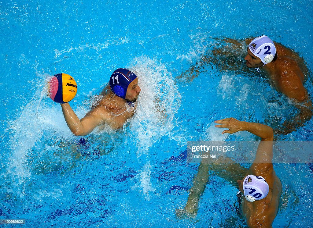 Andrija Prlainovic of Serbia controls the ball against Miklos GorNagy and Denes Varga of Hungary during the Fina Men's Water Polo World League Super...