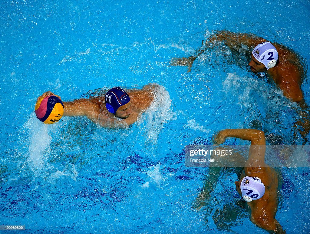 Andrija Prlainovic of Serbia controls the ball against Miklos Gor-Nagy and Denes Varga of Hungary during the Fina Men's Water Polo World League Super Final match between Hugary and Serbia at the Hamdan Sports Complex on June 21, 2014 in Dubai, United Arab Emirates.