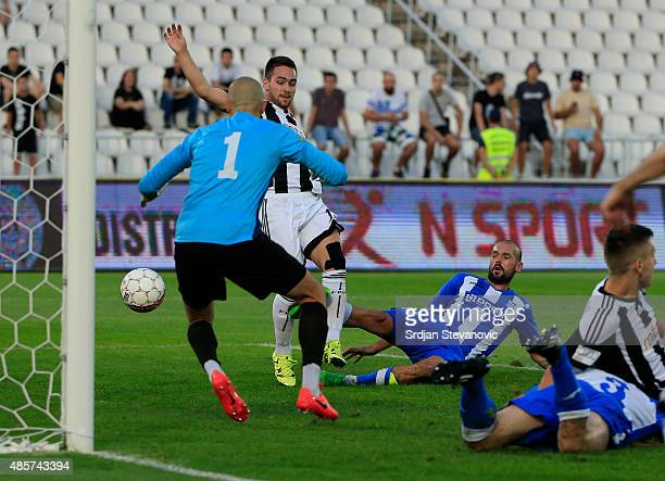 Andrija Zivkovic of FK Partizan scores the goal near Ivica Jovanovic and goalkeeper Stefan Cupic of OFK Belgrade during the Serbia Super League match...