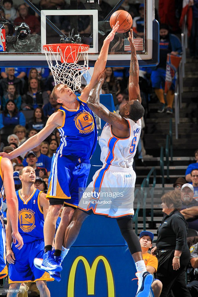 Andris Biedrins #15 of the Golden State Warriors contests a shot attempt by Kendrick Perkins #5 of the Oklahoma City Thunder on February 6, 2013 at the Chesapeake Energy Arena in Oklahoma City, Oklahoma.