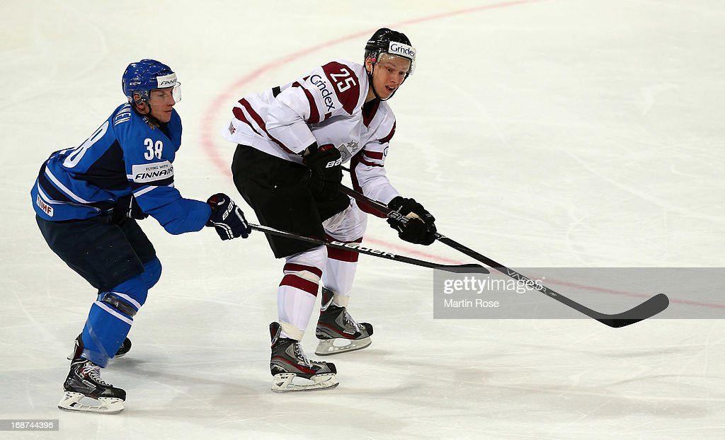 Andris Dzerins (R) of Latvia and Juuso Hietanen (L) of Finland battle for the puck during the IIHF World Championship group H match between Latvia and Finland at Hartwall Areena on May 14, 2013 in Helsinki, Finland.