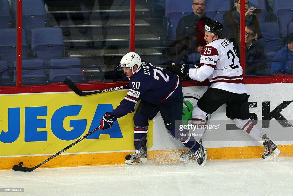 Andris Dzernis (R) of Latvia and <a gi-track='captionPersonalityLinkClicked' href=/galleries/search?phrase=Ryan+Carter+-+Eishockeyspieler&family=editorial&specificpeople=3144941 ng-click='$event.stopPropagation()'>Ryan Carter</a> (L) of USA battle for the puck during the IIHF World Championship group H match between Latvia and USA at Hartwall Areena on May 5, 2013 in Helsinki, Finland.
