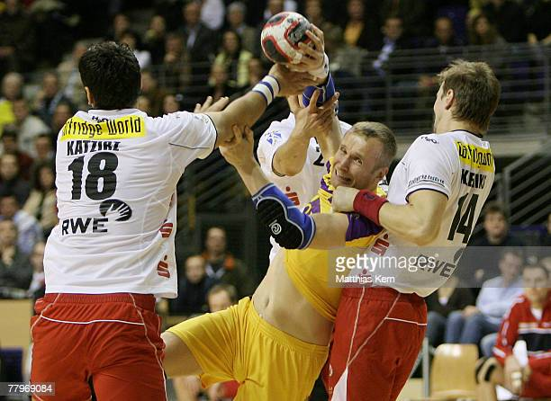 Andrius Stelmokas of Berlin is attacked by David Katzirz and Evars Klesniks of Essen during the Handball Bundesliga match between Fuechse Berlin and...