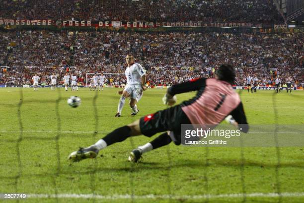 Andriy Shevchenko of Milan scores the winning goal from the penalty shoot out against Juventus FC goalkeeper Gianluigi Buffon during the UEFA...