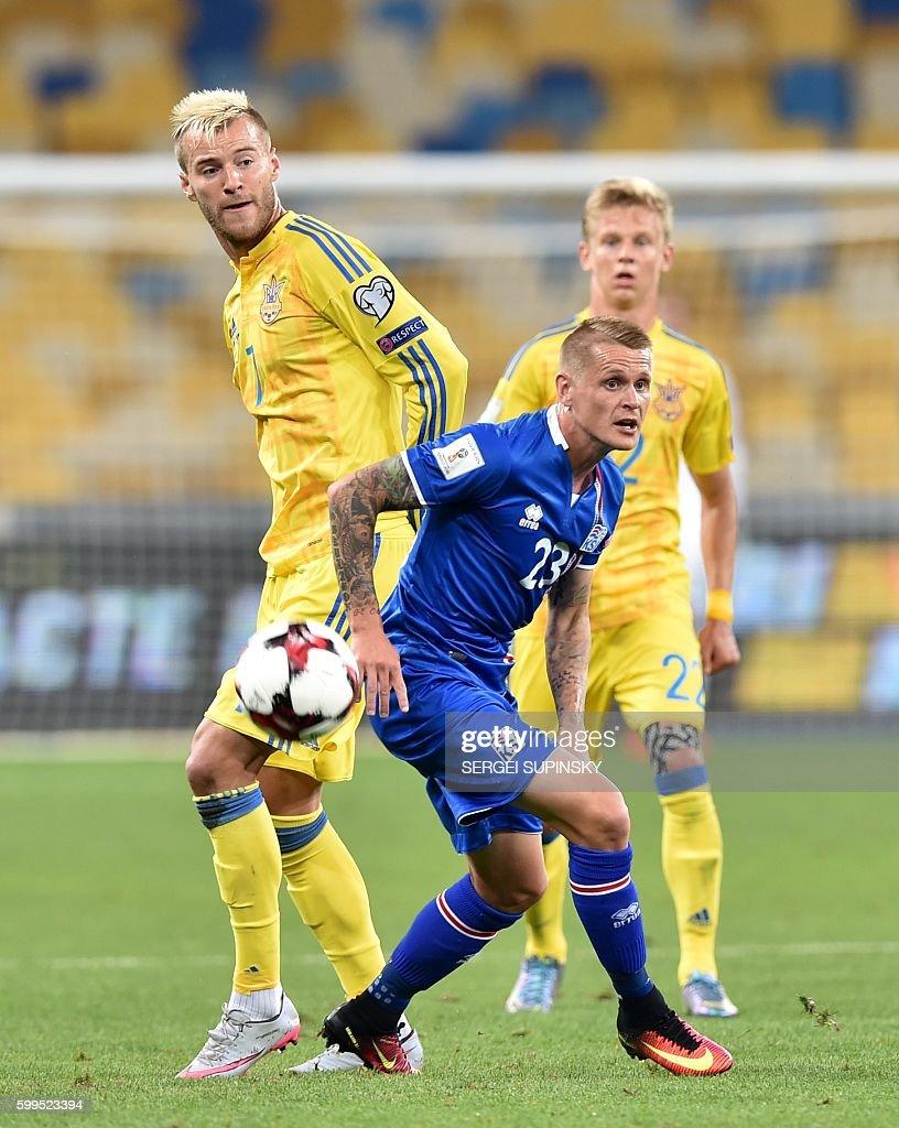 Andriy Yarmolenko L of Ukraine vies with Ari Freyr Skulason R