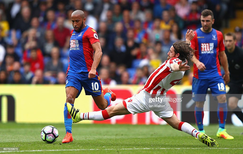 Andros Townsend of Crystal Palace (L) takes it past Joe Allen of Stoke City (R) as he attempts to slide him during the Premier League match between Crystal Palace and Stoke City at Selhurst Park on September 18, 2016 in London, England.