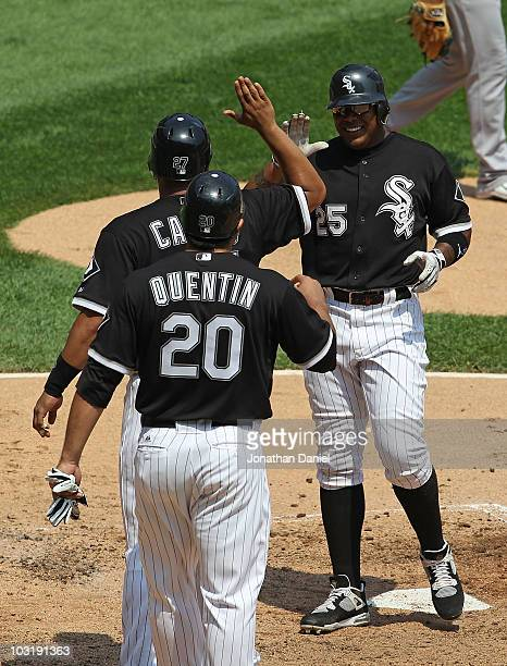 Andruw Jones of the Chicago White Sox is greeted at the plate by teammates Ramon Castro and Carlos Quentin after all three players scored runs in the...