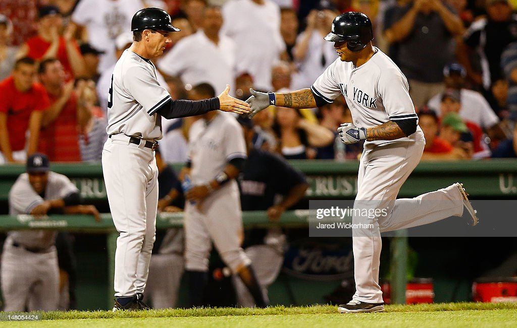Andruw Jones #22 of the New York Yankees is congratulated by third base coach Rob Thomson #59 after hitting a two run home run against the Boston Red Sox during the game on July 8, 2012 at Fenway Park in Boston, Massachusetts.