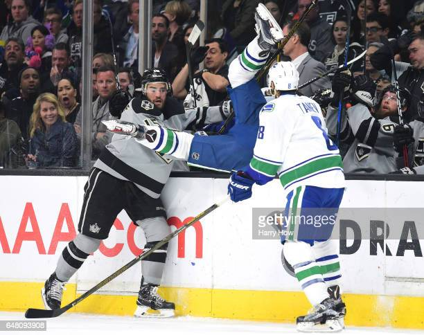 Andy Andreoff of the Los Angeles Kings knocks Jayson Megna of the Vancouver Canucks over the boards during the second period at Staples Center on...