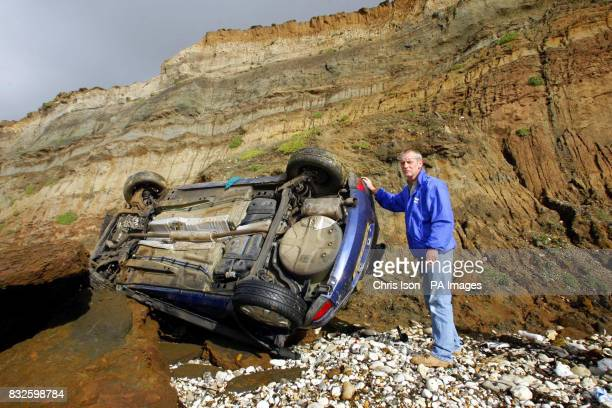 Andy Baldwin surveys the wreckage of his father's Vauxhall Corsa after he accidentally drove it over the edge of 80ft cliffs at Compton Bay on the...