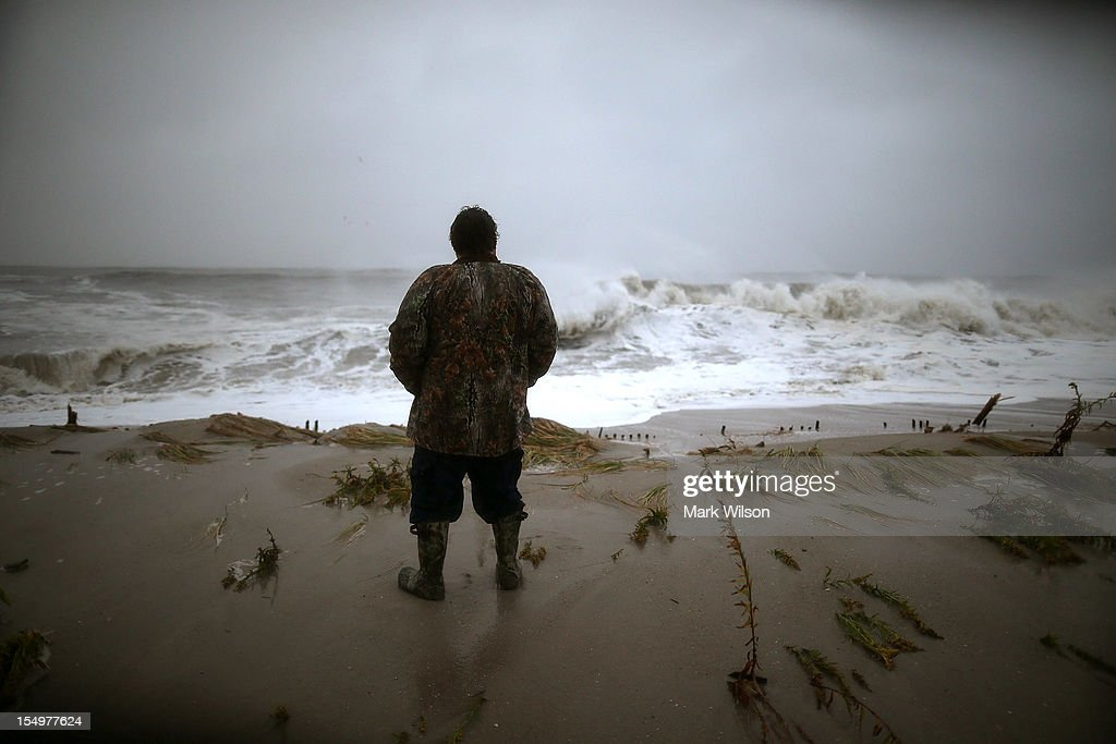 Andy Becica stands on the beach watching the heavy surf from Hurricane Sandy wash in in, on October 29, 2012 in Cape May, New Jersey. Later today the full force of Hurricane Sandy is expected to hit the New Jersey coastline bringing heavy winds and floodwaters.