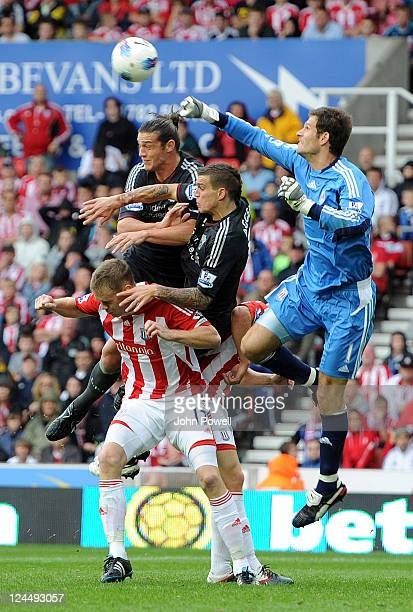 Andy Carroll and Daniel Agger of Liverpool both go up with Asmir Begovic and Ryan Shawscross of Stoke City during the Barclays Premier League match...