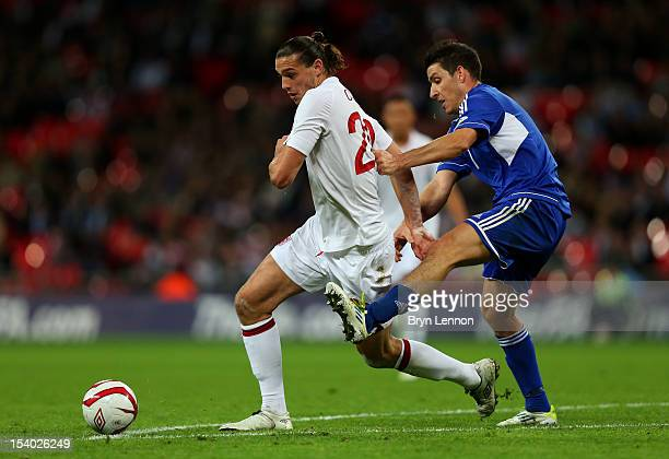 Andy Carroll of England competes for the ball with Alex Gasperoni of San Marino during the FIFA 2014 World Cup Group H qualifying match between...