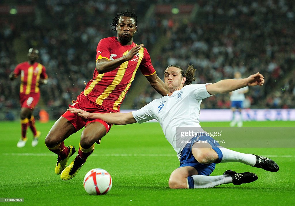 <a gi-track='captionPersonalityLinkClicked' href=/galleries/search?phrase=Andy+Carroll+-+Soccer+Player&family=editorial&specificpeople=1449090 ng-click='$event.stopPropagation()'>Andy Carroll</a> of England R) slides in front of Jonathan Mensah, captain of Ghana during the international friendly match between England and Ghana at Wembley Stadium on March 29, 2011 in London, England.