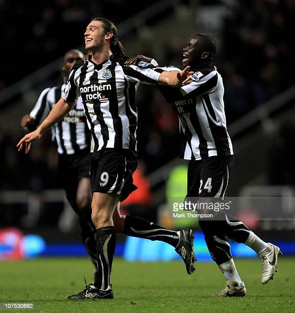 Andy Carroll of Newcastle United celebrates scoring his team's third goal with team mate Cheik Tiote during the Barclays Premier League match between...