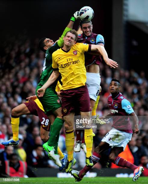 Andy Carroll of West Ham is kept at bay by goalkeeper Vito Mannone and Per Mertesacker of Arsenal during the Barclays Premier League match between...