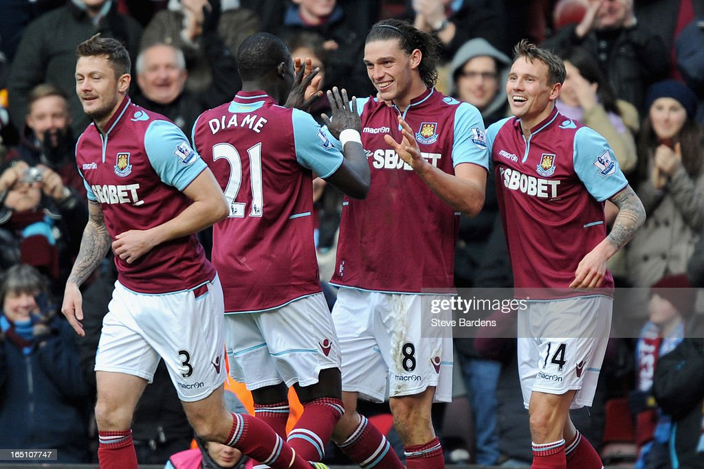 Andy Carroll of West Ham United (C) celebrates scoring his second goal and his team's third with teammates Mohamed Diame (second left) and Matthew Taylor (R) during the Barclays Premier League match between West Ham United and West Bromwich Albion at the Boleyn Ground on March 30, 2013 in London, England.