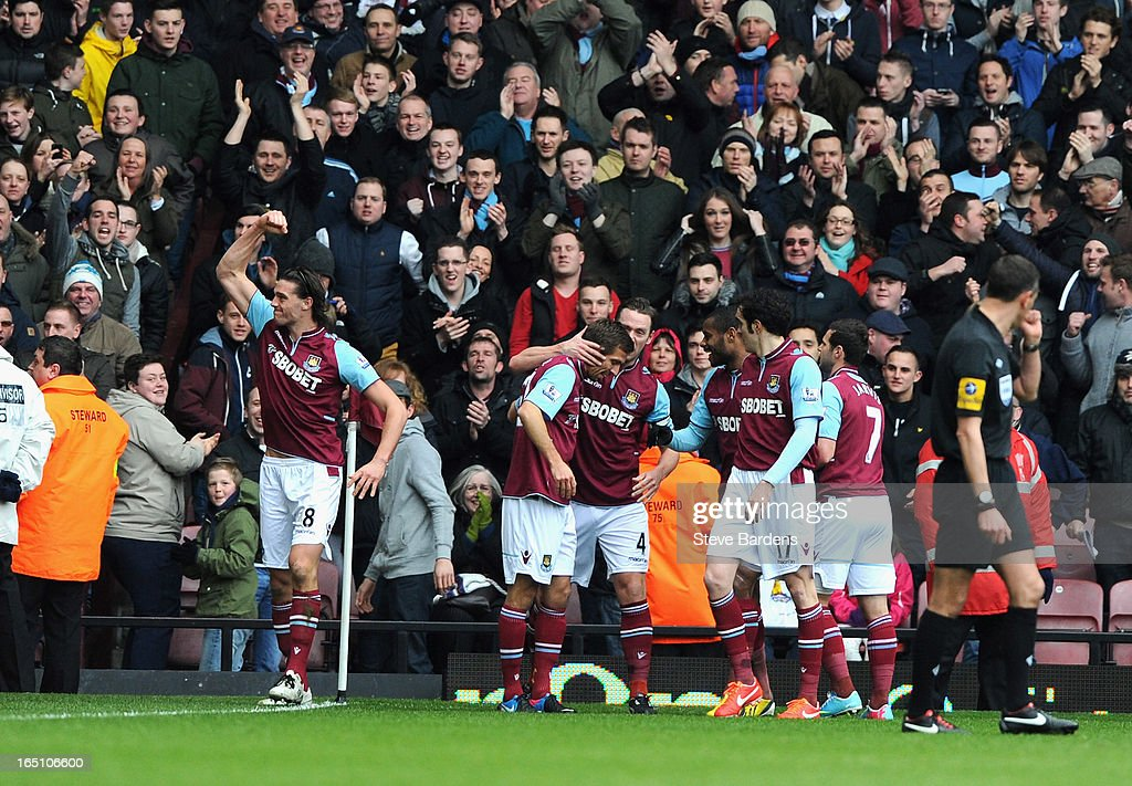 Andy Carroll of West Ham United (L) celebrates scoring the opening goal with team mates during the Barclays Premier League match between West Ham United and West Bromwich Albion at the Boleyn Ground on March 30, 2013 in London, England.