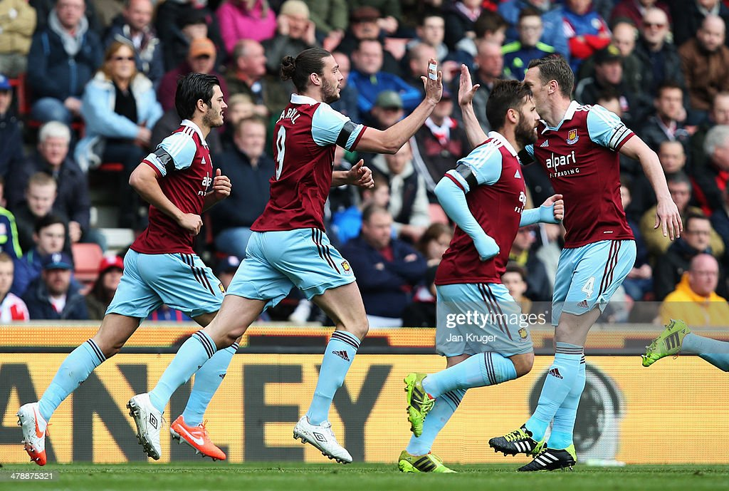 Andy Carroll of West Ham United (2R) celebrates with team mates as he scores their first goal during the Barclays Premier League match between Stoke City and West Ham United at Britannia Stadium on March 15, 2014 in Stoke on Trent, England.