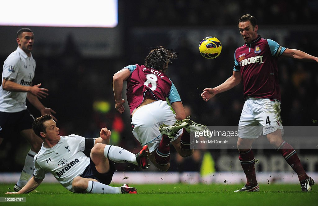 Andy Carroll of West Ham United goes to ground under a challenge from Scott Parker of Tottenham Hotspur leading to a penalty during the Barclays Premier League match between West Ham United and Tottenham Hotspur at the Boleyn Ground on February 25, 2013 in London, England.