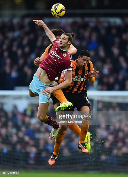 Andy Carroll of West Ham United heads the ball with Alex Bruce and Curtis Davies of Hull City during the Barclays Premier League match between West...