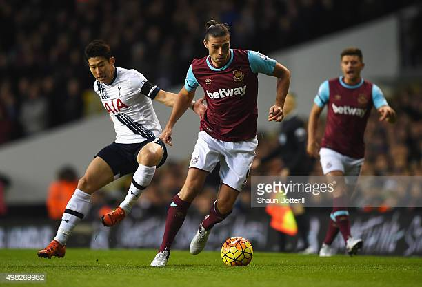 Andy Carroll of West Ham United is challenged by HeungMin Son of Tottenham Hotspur during the Barclays Premier League match between Tottenham Hotspur...