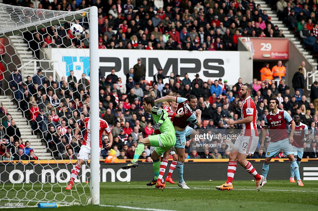 Andy Carroll of West Ham United outjumps Asmir Begovic of Stoke City to score their first goal with a header during the Barclays Premier League match between Stoke City and West Ham United at Britannia Stadium on March 15, 2014 in Stoke on Trent, England.