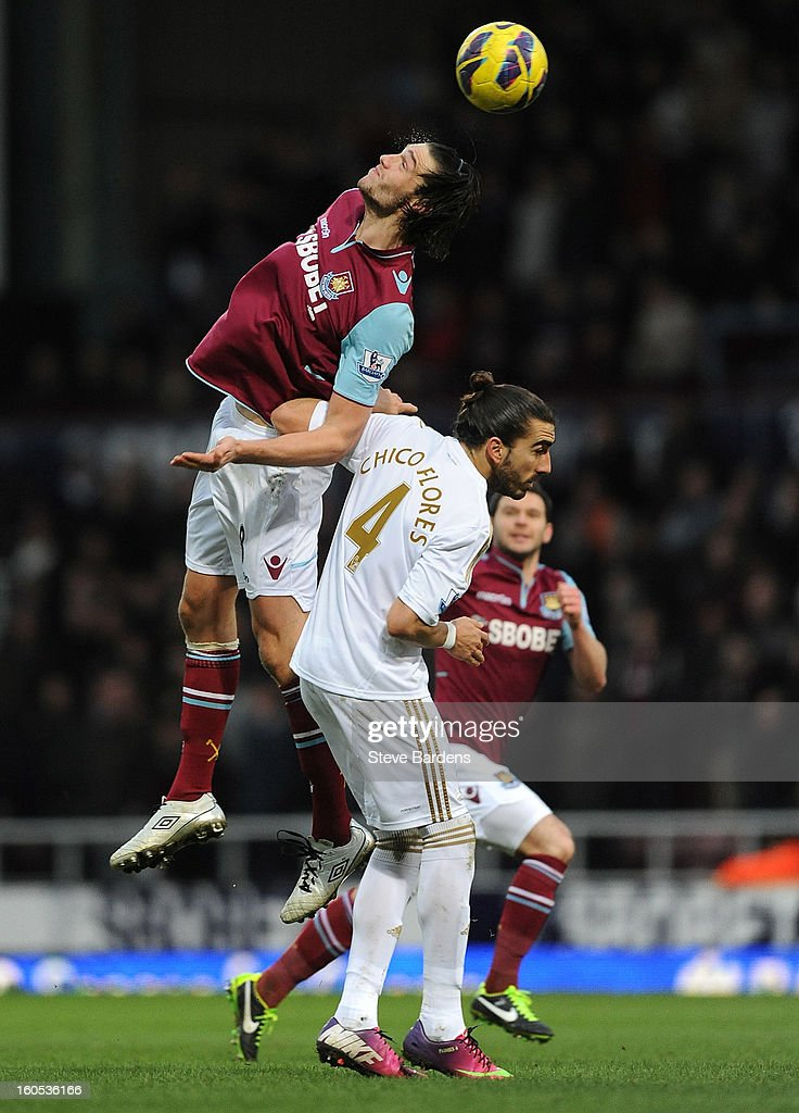Andy Carroll of West Ham United wins a header from Chico Flores of Swansea City during the Barclays Premier League match between West Ham United and Swansea at the Boleyn Ground on February 2, 2013 in London, England.